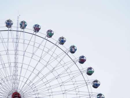 Abstract background, Ferris wheel with booths against the sky, space for text.
