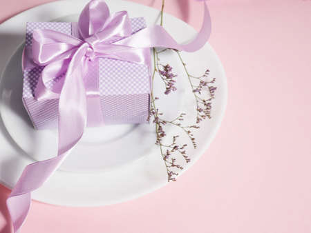 A gift box with a lilac ribbon lies on the plates saucers.