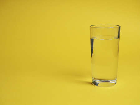 minimalistic concept of water consumption, one glass of water on a yellow background. 版權商用圖片