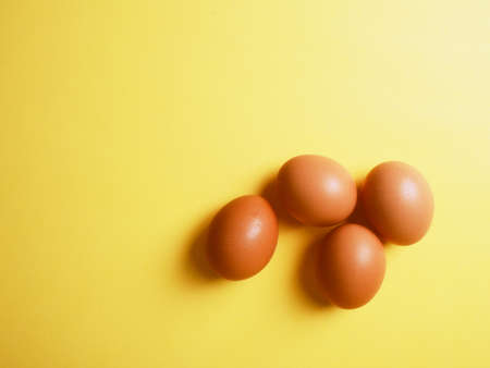 Banner brown eggs on a yellow background with a shadow, modern Easter concept, hidden trend of the year, website banner.