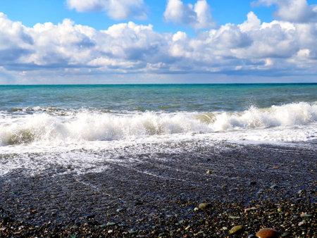 Summer seascape, sea and waves, clear blue sky, stone beach. 版權商用圖片