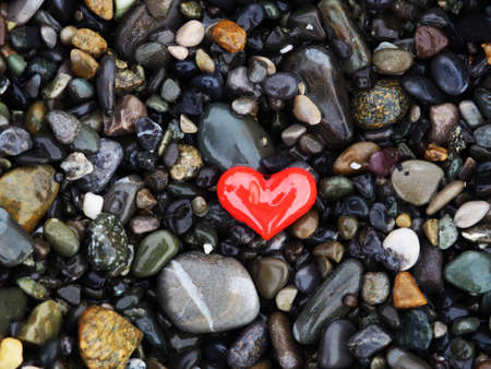 One small red heart lies on the black sea rocks. 版權商用圖片