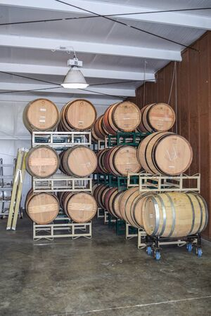 Stacked Wine Barrels, with one hanging light and a beamed ceiling