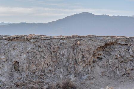 夕暮れ時の山のシルエットと多孔質の岩の壁