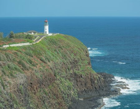 Far off shot of the Kilauea Lighthouse, the ocean and a shear cliff, on Kauai, Hawaii