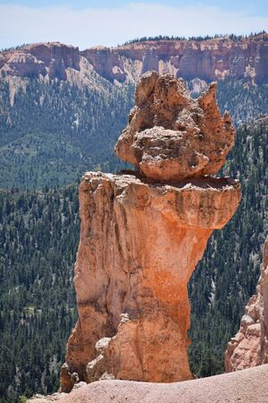 Interesting red rock formation with mountains and green trees in the background, in Bryce Canyon National Park, Utah