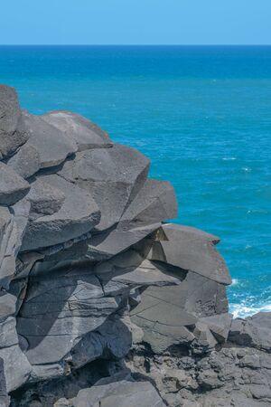 灰色のギザギザの岩と美しい青い海、地平線、水色の空