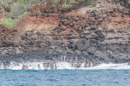Lava rock cliff with red dirt, and the ocean Imagens