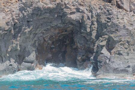 El océano y una pequeña ola entrando en una cueva de lava natural. Foto de archivo - 83593684