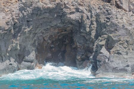 The ocean, and a small wave entering a natural lava cave Imagens