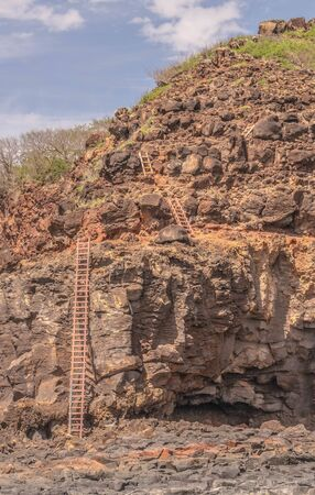 Series of wooden ladders trailing down a cliff side