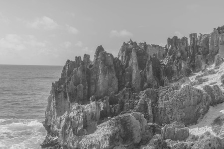 Black and white shot of jagged Stone Formations on the coastline, with ocean water