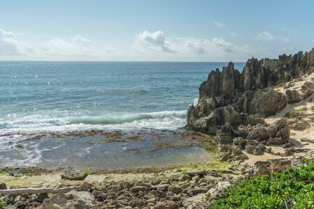 Rocky beach with green shrubs, breaking waves and interesting stone formations above, along the Heritage Trail, on Kauai Imagens
