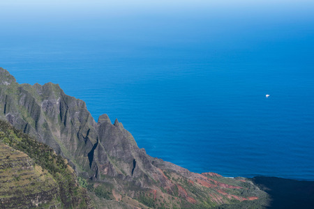 Partial view of a slopped mountain on the Napali Coast and the deep blue ocean, from the Kalalau Lookout, on Kauai