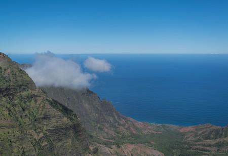 Napali Coastline, hillside, ocean, ocean horizon, blue sky and a wispy cloud, from the Kalalau Lookout, on Kauai Stock Photo