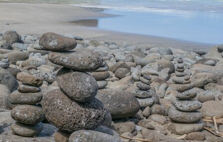 sized: Sandy beach, with multiple-sized stacked stones in the foreground