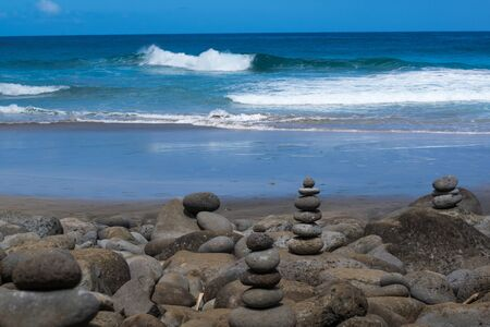 Ocean waves, sandy beach, and stacked stone Stock fotó