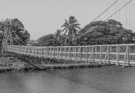 Historic pedestrian swinging bridge in Old Hanapepe Town, in black and white, on Kauai