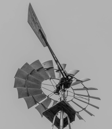 Top portion of an old water mill spinner with fan blades, in black and white