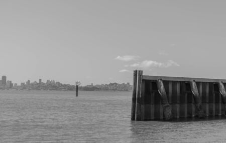 Black and white photo of a sea wall, the San Francisco Bay and part of San Francisco