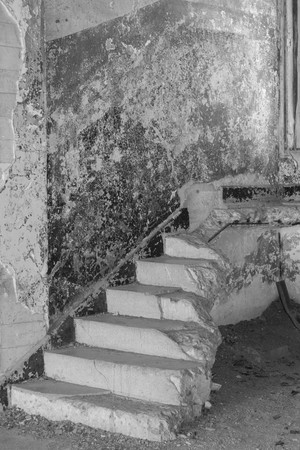 Black and white shot of stairs leading to nowhere, in an abandoned building
