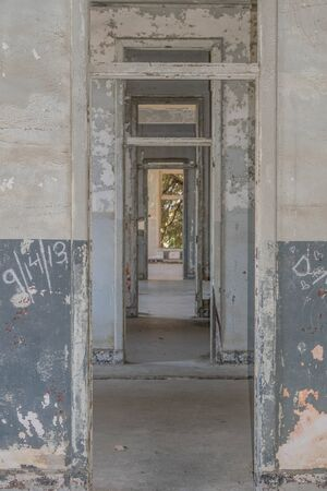 Looking through multiple door frames, with layers of chipping paint, in an old abandoned building