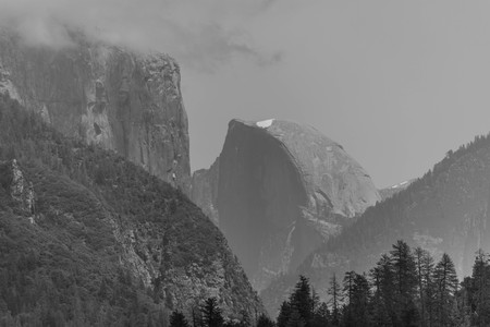 Black and white shot of half dome with a spot of snow at the top, and surrounding mountains, in Yosemite National Park