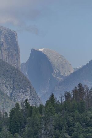 Side view of half dome with a spot of snow at the top, surrounding mountains and a pine forest in the foreground, in Yosemite National Park