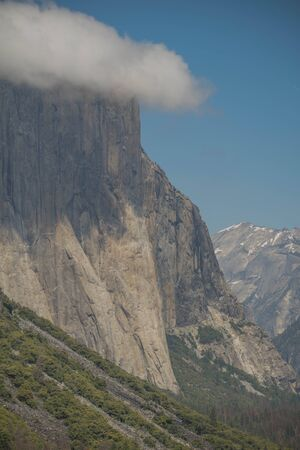 Side view of El Capitan, with shrubs, a blue sky and a puffy cloud, in Yosemite National Park