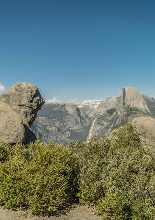 Bushes, a boulder, and half dome and other mountains in the background, on the Glacier Point Trail, in Yosemite national park