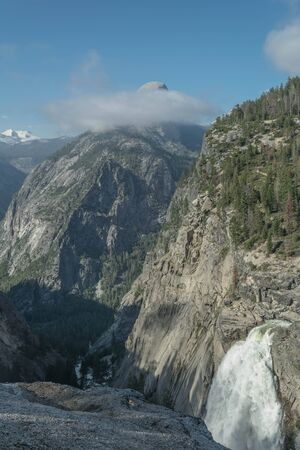 Partial view of the Illilouette waterfall, mountains and cloudy blue sky, in Yosemite National Park