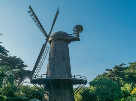 Upper half of The Dutch Windmill, green trees and a blue sky, in Golden Gate Park, San Francisco
