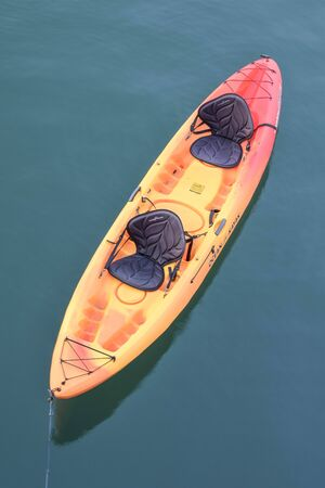 Close up of a colorful, empty ocean kayak on the water