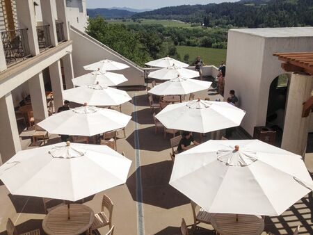White sun umbrellas on the deck at Sterling Winery in the early afternoon, Napa Valley, California