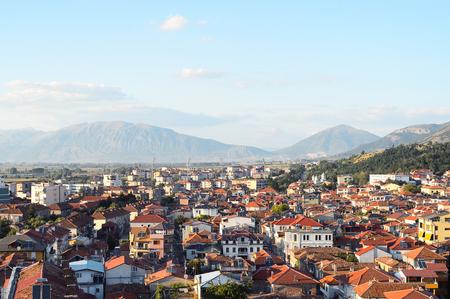 Panoramische luchtmening aan Korca, de stad in zuidwesten van Albanië, de bergen en de rode tegeldaken van zijn gebouwen.