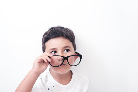 Serious little boy looking from under his huge glasses. High key and white background. Stock Photo