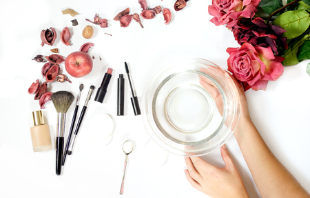 female skincare flatlay composition to soften tap water with soda combined with women items: make up brushes, flowers and hands