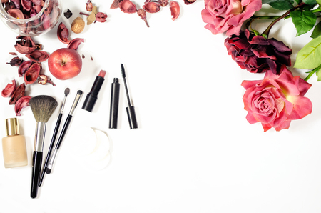 female skincare flatlay composition with with women items: make up brushes, flowers and petals Stock Photo