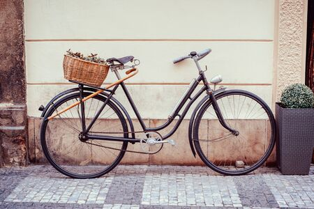 Vintage bicycle with an old basket at the back of it left in the street of Prague's old town. Banque d'images