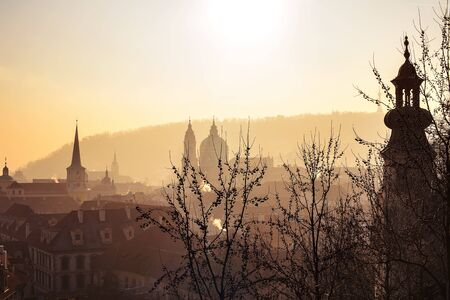 Prague's gothic architecture silhouettes in sunset and foggy light. View from Prague Castle.