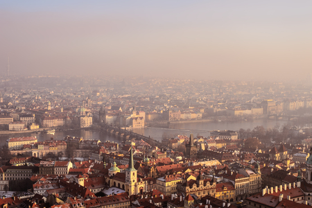 Aerial view to Prague buildings and the city from Prague Castle on a foggy day.