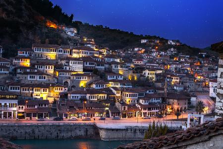 Avondmening naar Berat, historische stad in het zuiden van Albanië 's nachts met alle knipperende lichten en witte huizen die zich op een heuvel verzamelen. Gevangen tijdens het blauwe uur met de hemel vol sterren. Stockfoto