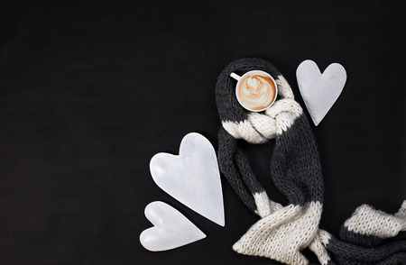 Valentines day morning top view composition with hearts and a cup of cappuccino covered with wool scarf