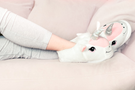 feet female wearing unicorn trendy slippers laying on counch, soft pastel colours beige and pink Archivio Fotografico