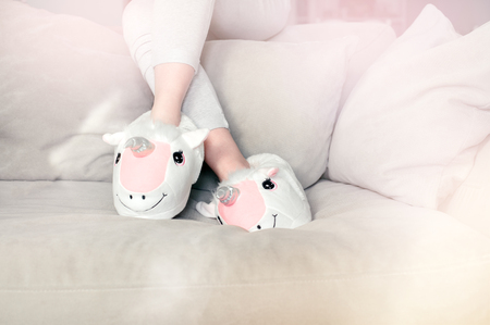 feet female wearing unicorn trendy slippers sitting on counch, soft pastel colours beige and pink Stock Photo