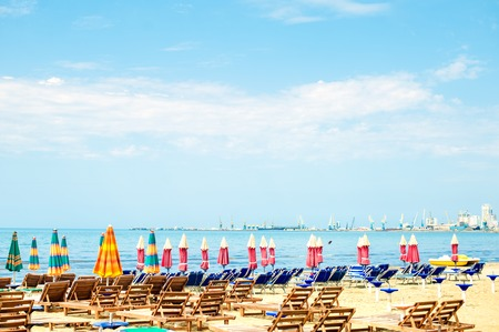 Vista aérea de la playa de arena del mar Adriático en Albania, llena de sombrillas y hamacas, Puerto de Durres en el horizonte