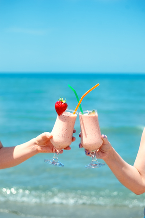 Two fruit juice smoothie in classic glass cups of berry fruits on summer turquois sea water background.