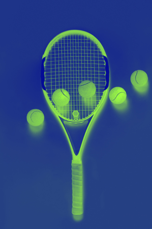 Closeup on ball on a tennis racket green and blue duotone