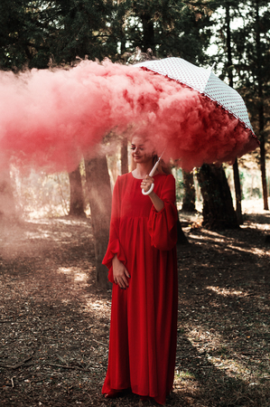 Attractive woman with a colorful smoke grenade bomb fashion