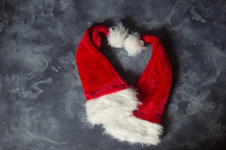 Top view two Santa hats in a shape of heart on black concrete board background, Christmas Eve festival Stockfoto